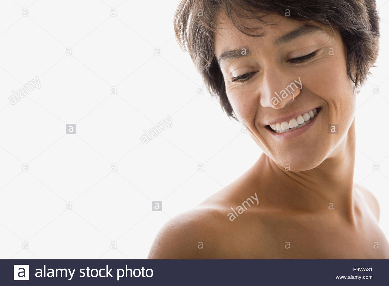 Smiling woman with bare chest looking down - Stock Image