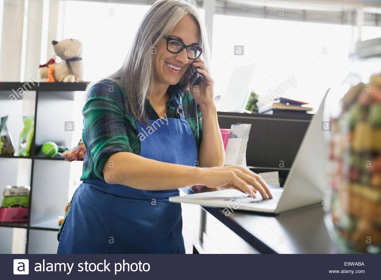 Dog daycare owner on telephone using laptop - Stock Image