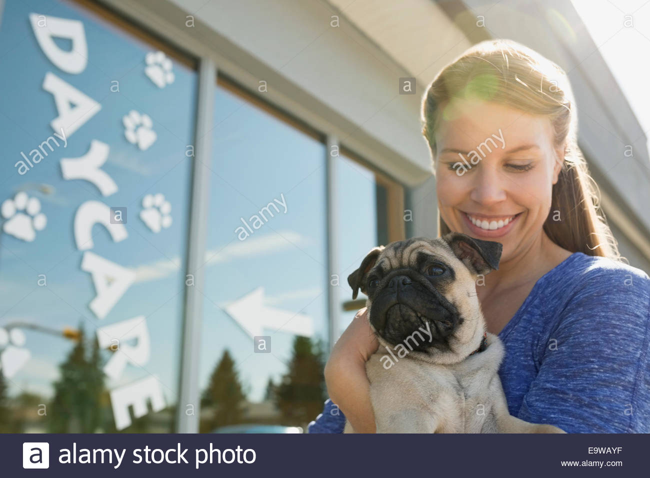 Woman with Pug outside dog daycare - Stock Image