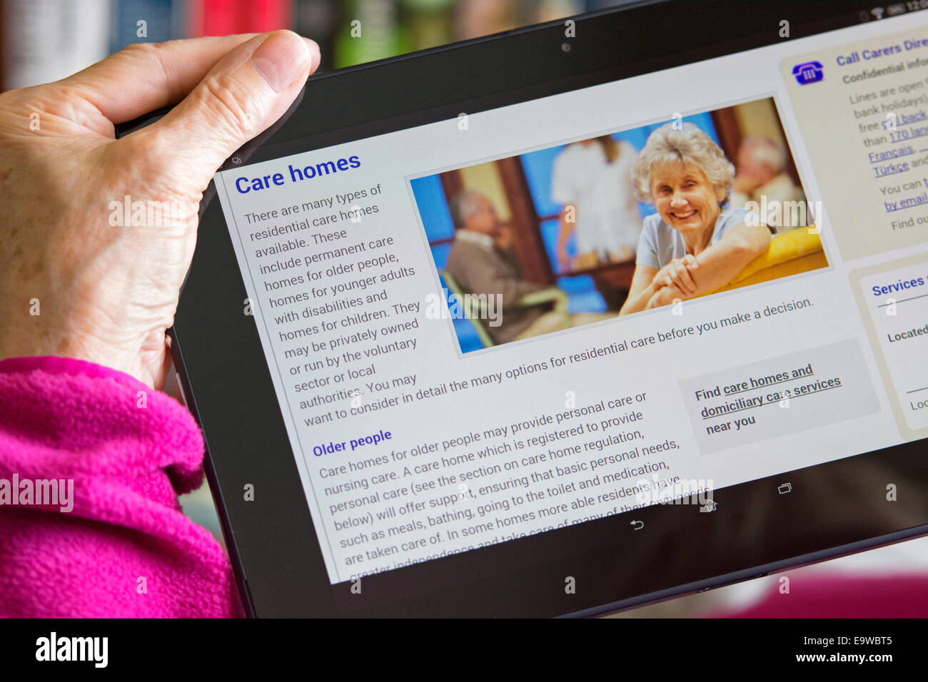 Care Home, Care Services screen on NHS Website, Woman reading Browsing Web Site for Care Homes - Stock Image