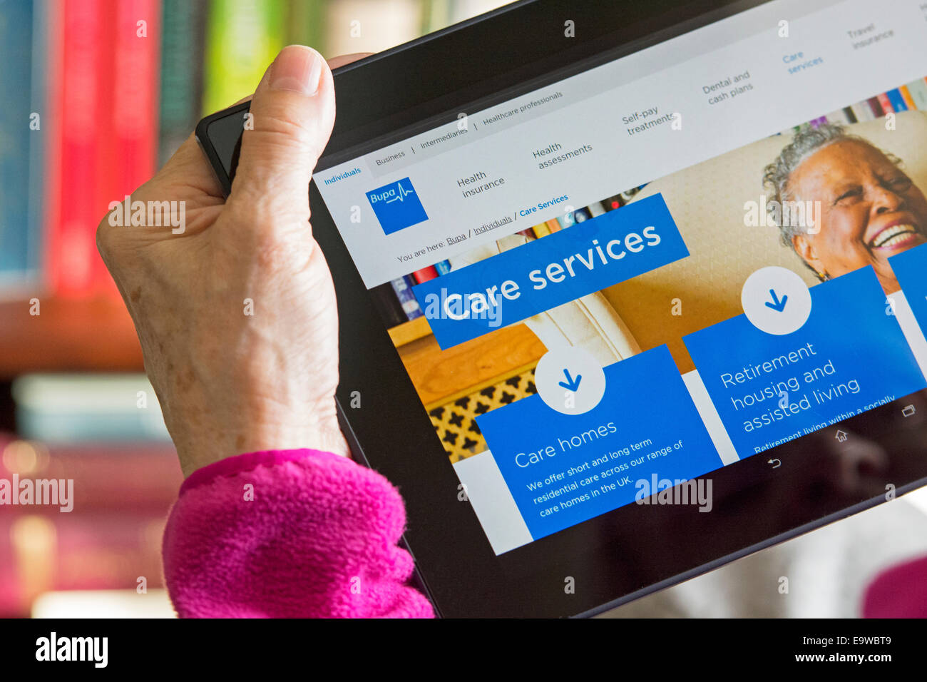 Care Home, Care Services screen on Bupa Website, Woman reading Browsing Web Site for Care Homes - Stock Image