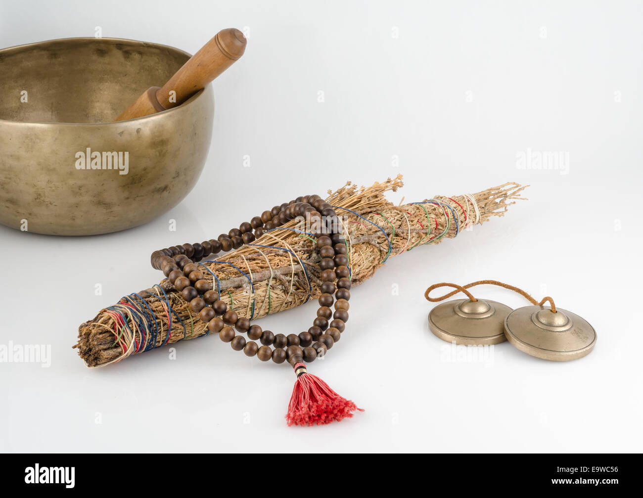 Hand Made Singing Bowl with Ringing Stick, Prayer Beads, Meditation Bells and Smudge Stick. - Stock Image