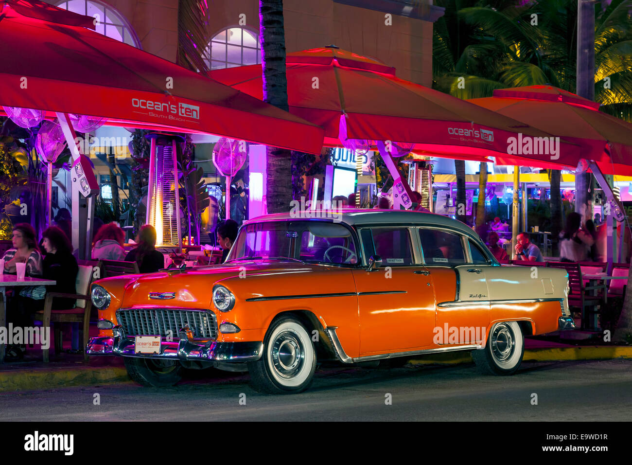 Orange and white two-tone 1955 Chevy Chevrolet Bel Air 4-door sedan parked in front of Ocean's Ten on Deco Drive, Stock Photo