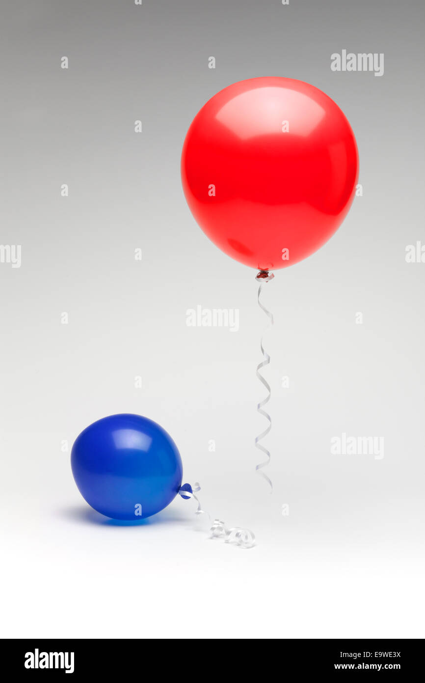 A red republican balloon floating over a partially deflated  blue democratic balloon. - Stock Image