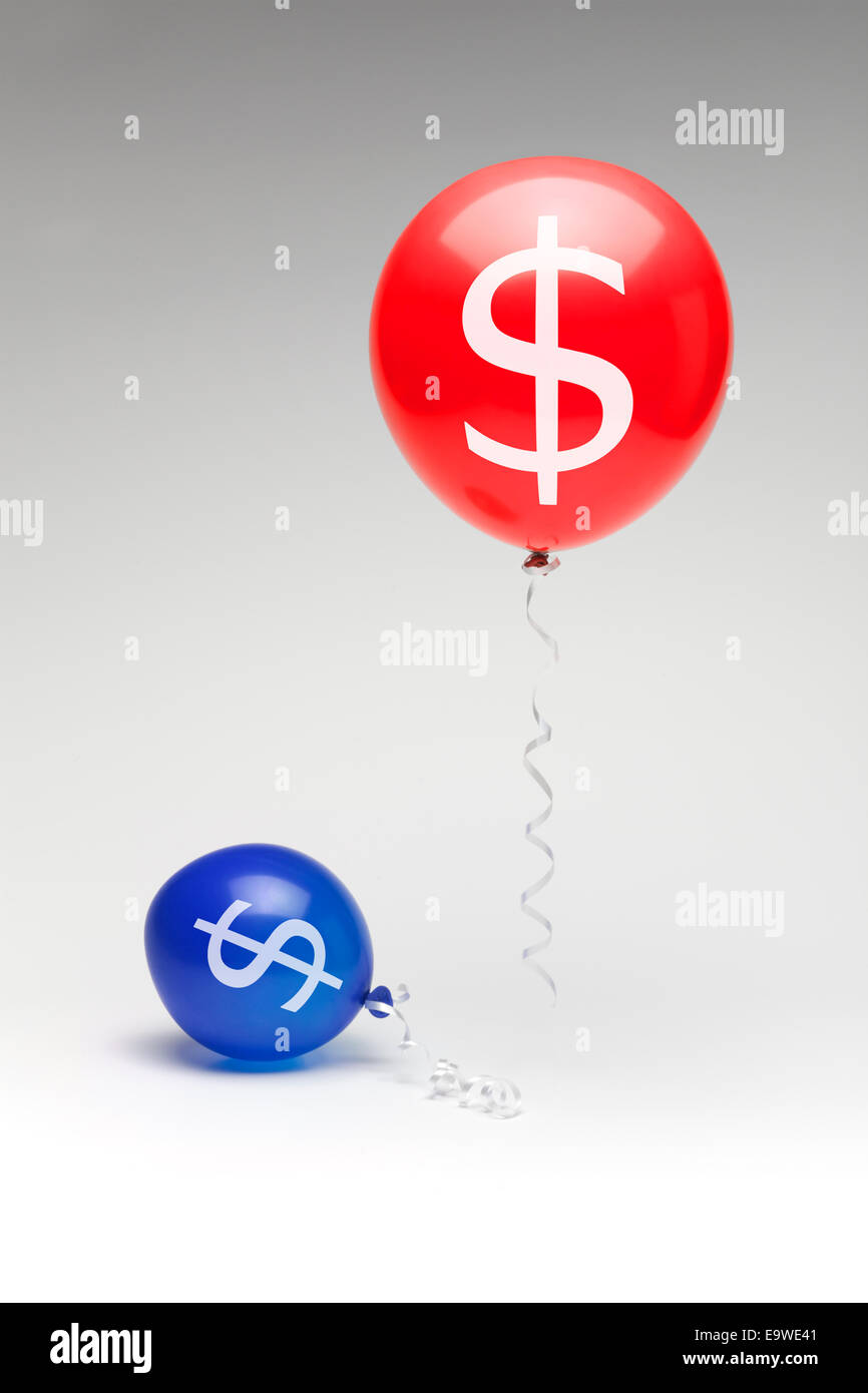 A red republican balloon floating over a partially deflated  blue democratic balloon with dollar signs. - Stock Image