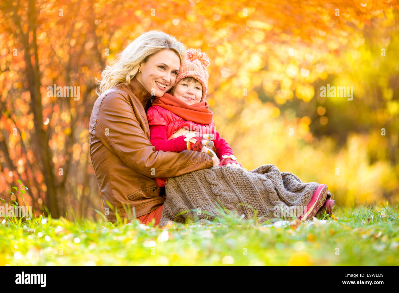 Happy mother and child outdoor in autumn park - Stock Image