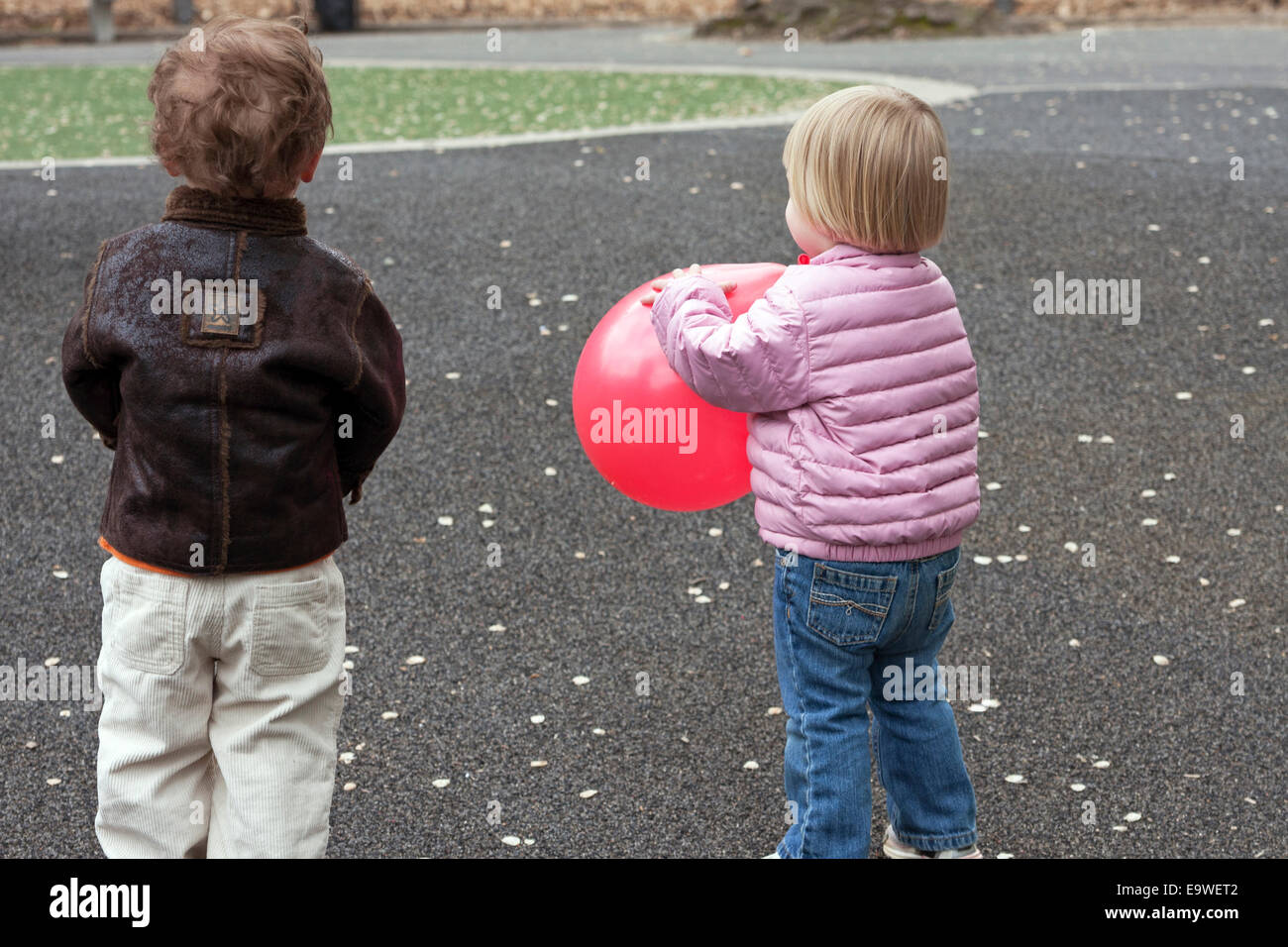 Two year olds play together in Central Park in New York City. - Stock Image