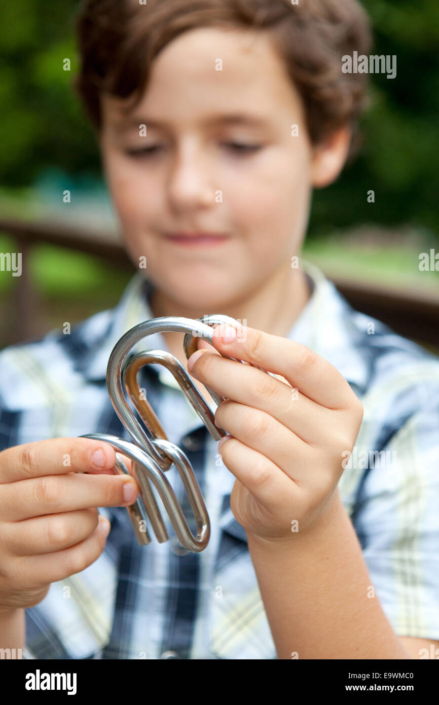 Young boy playing with a metal puzzle - Stock Image
