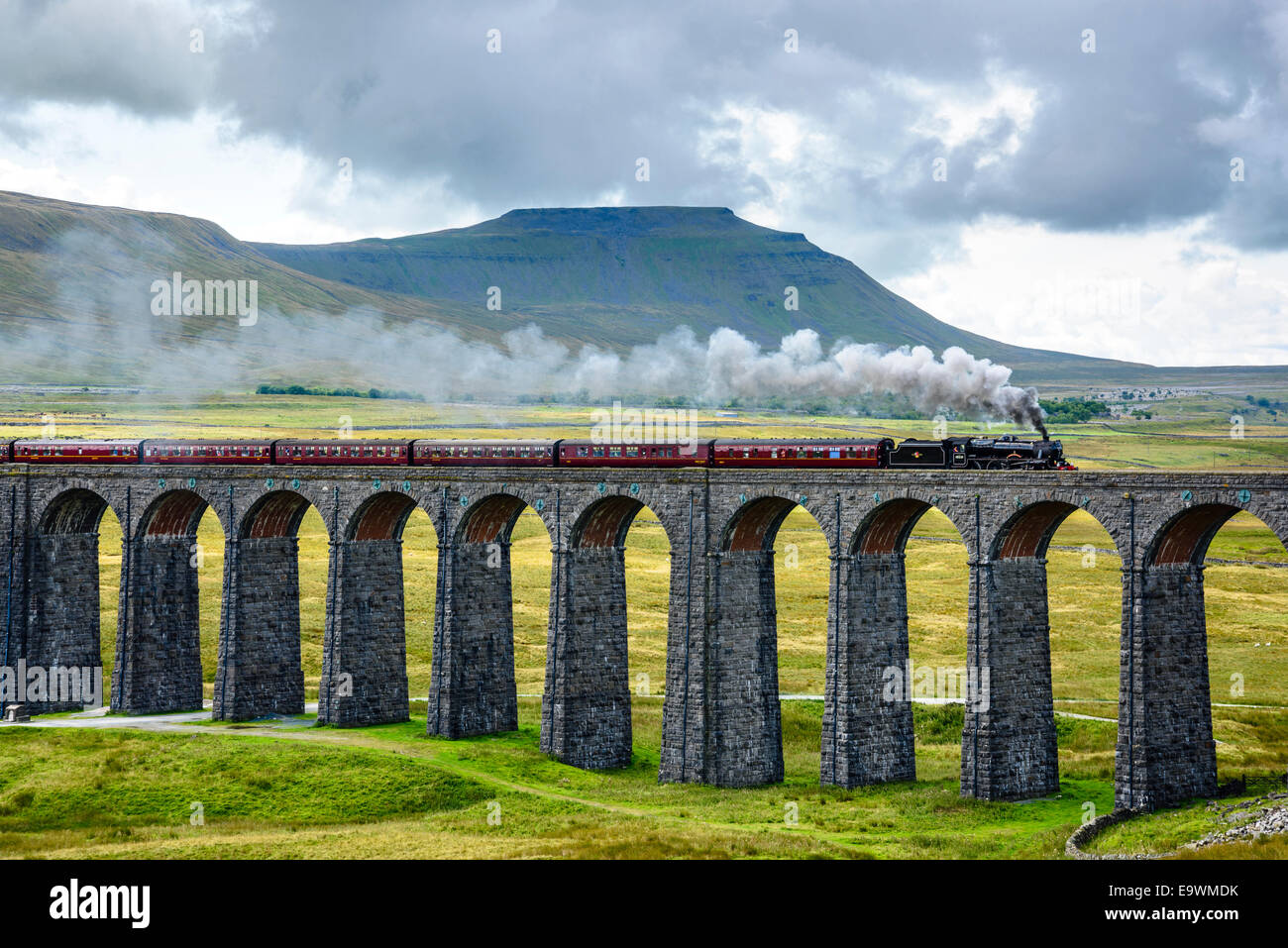Steam train crossing the Ribblehead Viaduct on the Settle-Carlisle railway line with Ingleborough behind - Stock Image