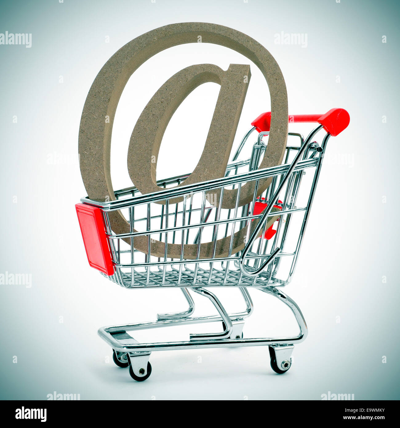 an at sign in a shopping cart, depicting the concept of e-shopping or e-commerce - Stock Image
