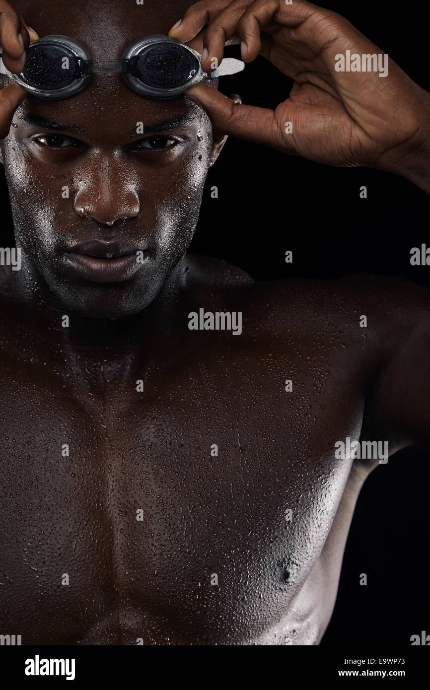 Close-up image of young male swimmer with goggles. African man with swimming glasses against black background. - Stock Image