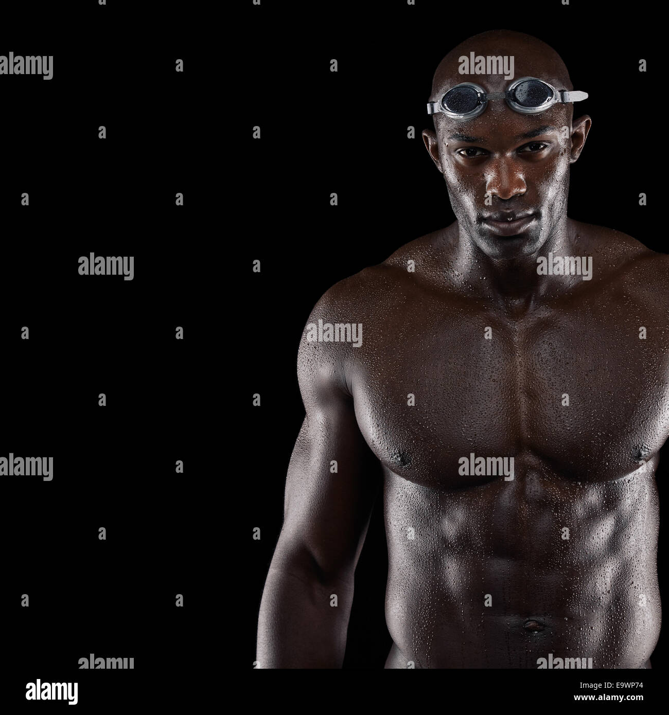 Studio shot of professional male swimmer with copy space. Young African man with muscular build wearing swimming - Stock Image