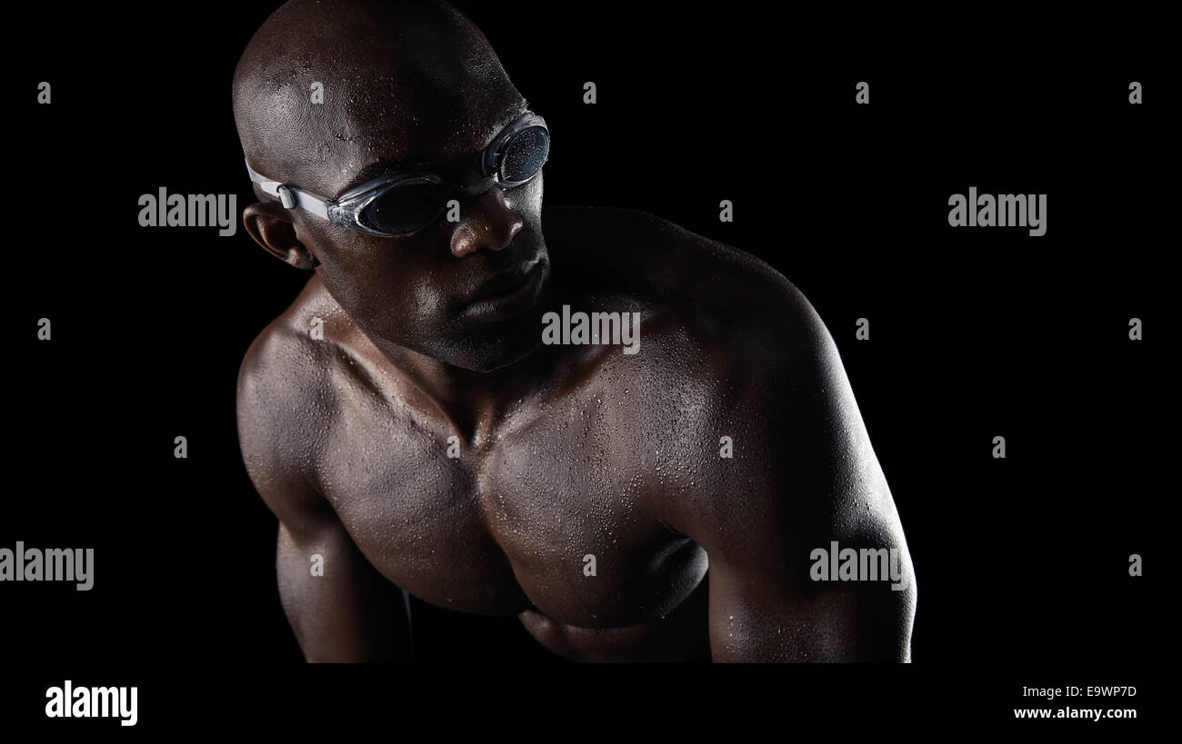 Studio shot of African male swimmer wearing goggles looking over shoulder against black background. Muscular young - Stock Image