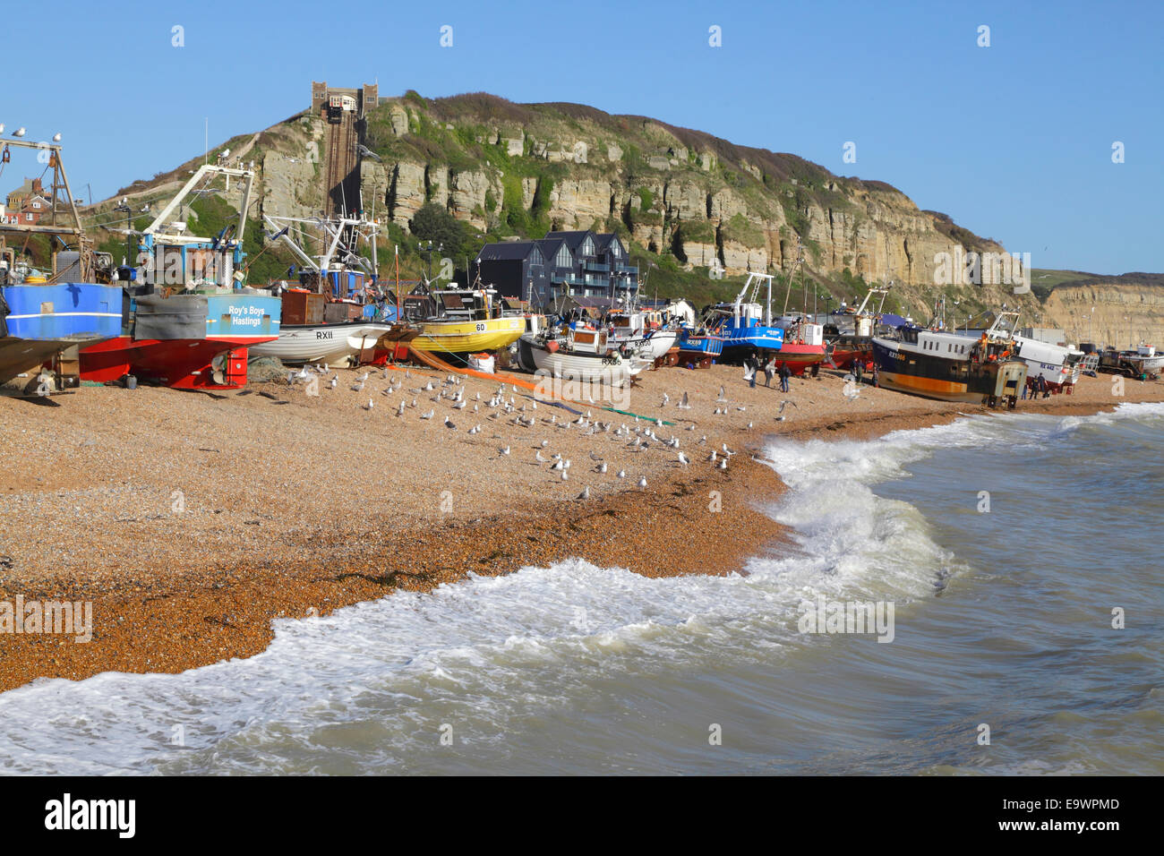 Fishing boats landing on Hastings Old Town Stade beach. Hastings has the biggest beach launched fishing fleet in - Stock Image