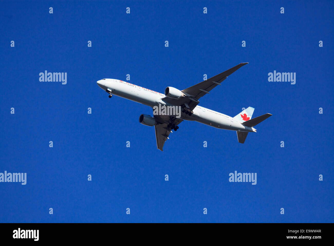Air Canada Boeing 777-333(ER) from underneath against blue sky with undercarriage down - Stock Image