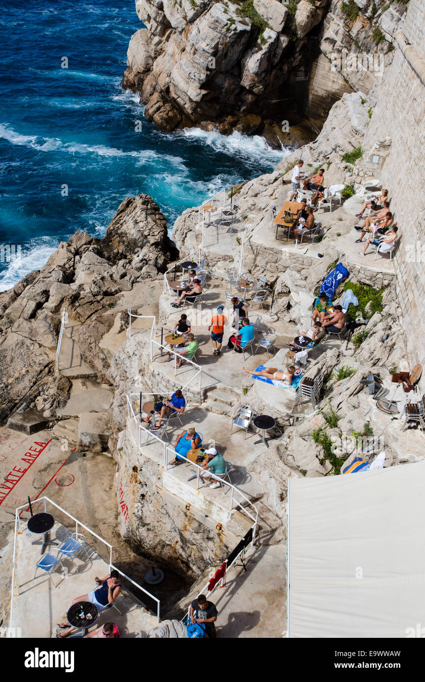 Tourists relax, sunbathe and swim along the base of the city walls in Dubrovnik Old Town. - Stock Image