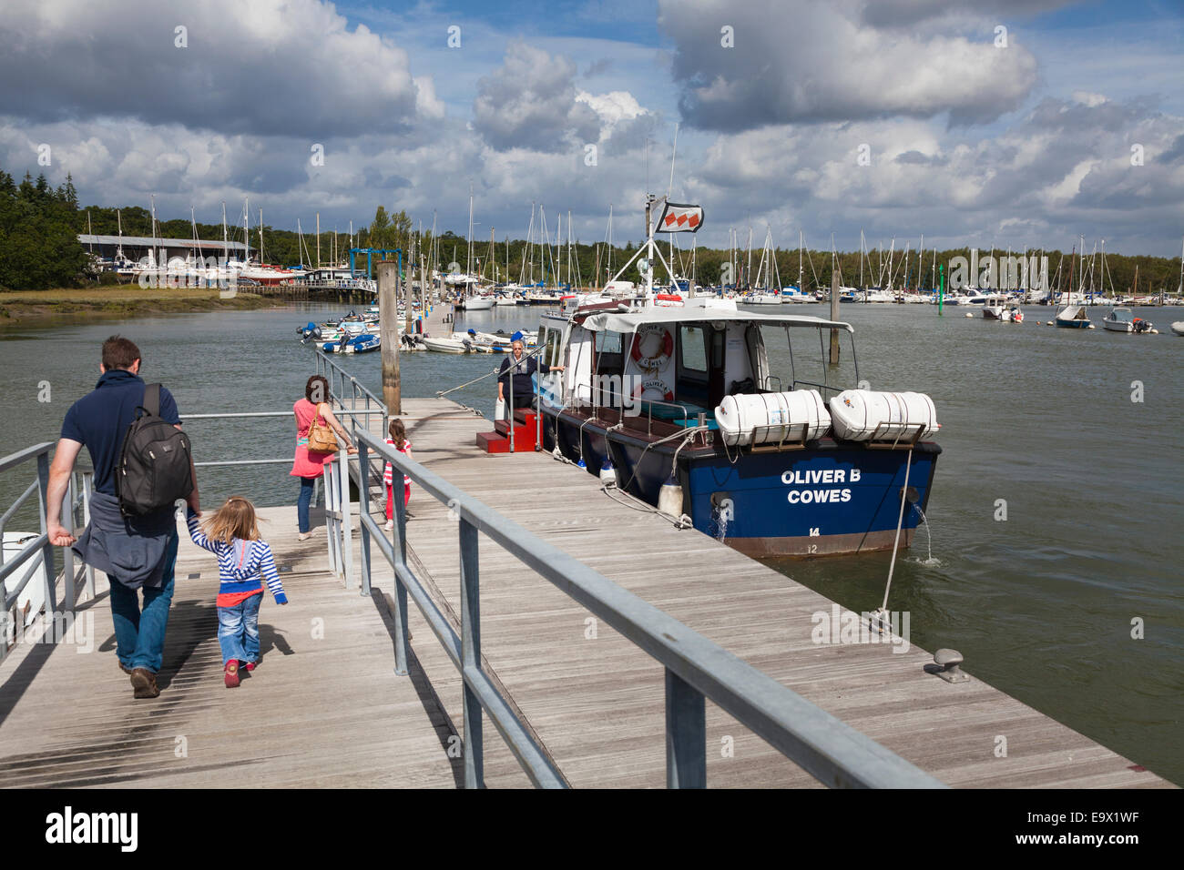 Family walking down jetty to river cruise boat on the Beaulieu River Stock Photo