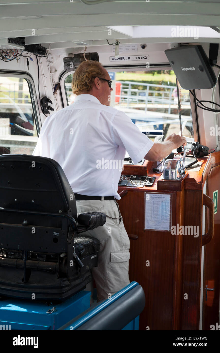 Skipper operating controls of motor boat river cruiser Stock Photo