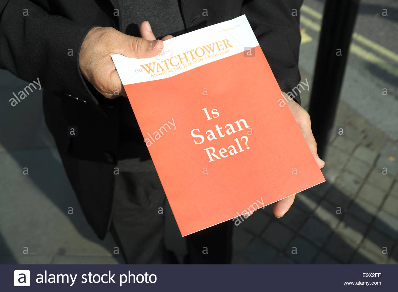 An edition of 'The Watchtower Announcing Jehovah's Kingdom' magazine , being handed out in the street - Stock Image