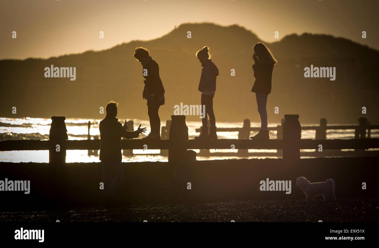 Children walking along a breakwater on Littlehampton Beach at sunset accompanied by their dog - Stock Image