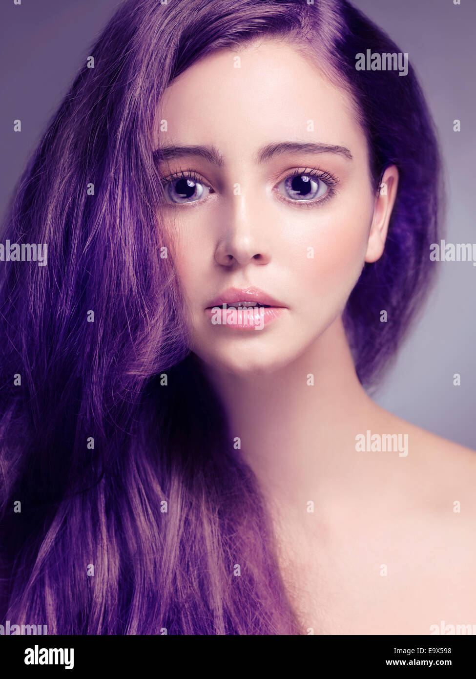 Cute young woman face with big sad eyes and long purple hair Stock