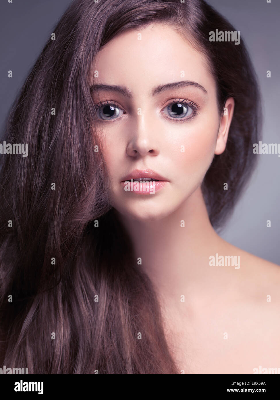 Cute young woman face with big gray eyes and long brown hair