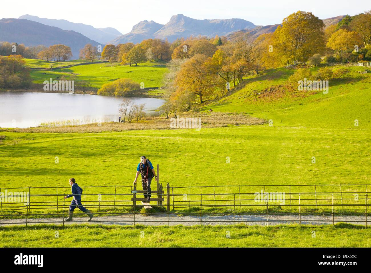 Tourists stepping over a style alongside a footpath at Loughrigg Tarn, The Lake District, Cumbria, England, UK. - Stock Image