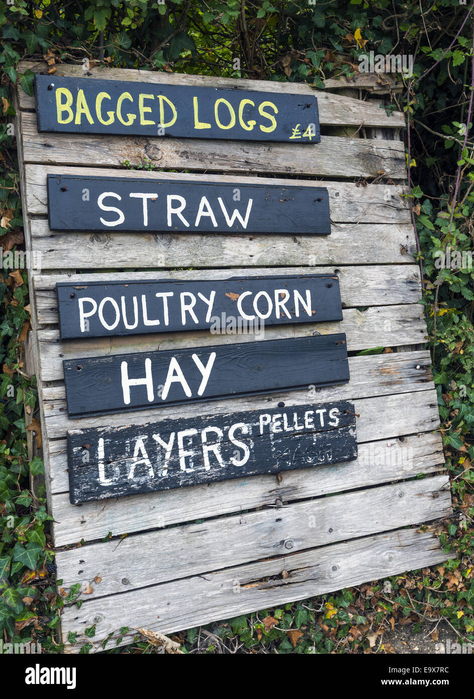 Roadside pallet farm sign for bagged logs, straw, poultry corn, hay and layers - Stock Image