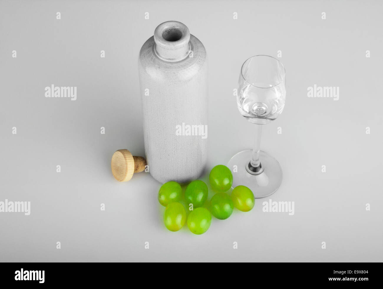 Grappa with traditional stoneware bottle and grapes - Stock Image