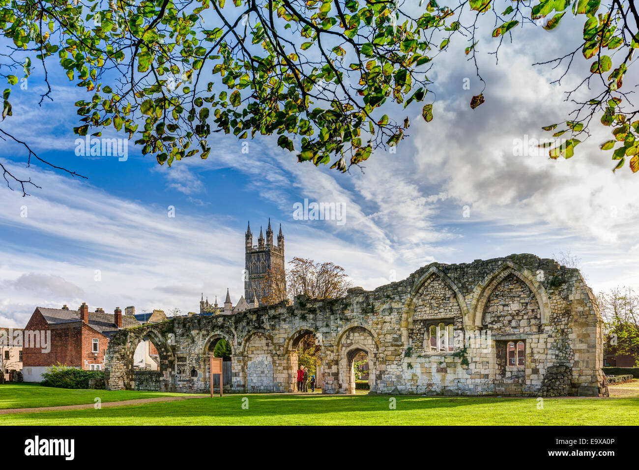 Gloucester cathedral rises above the ruins of St Oswald's priory, bathed in autumn sunshine, in the city of - Stock Image