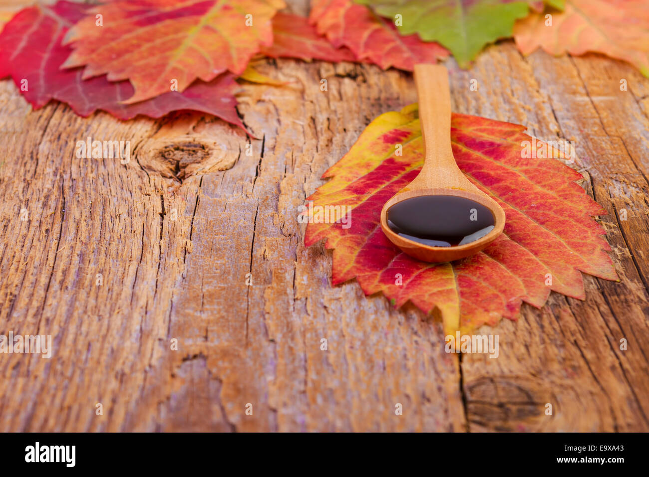leaf and syrup in wooden spoon on wooden background - Stock Image