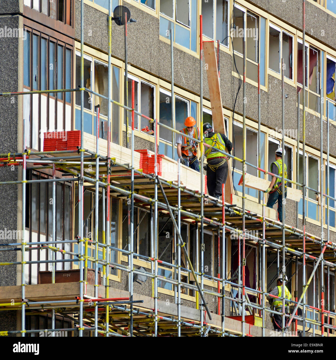 Scaffolders working on one of the empty Heygate Estate high rise social housing blocks in preparation for regeneration - Stock Image
