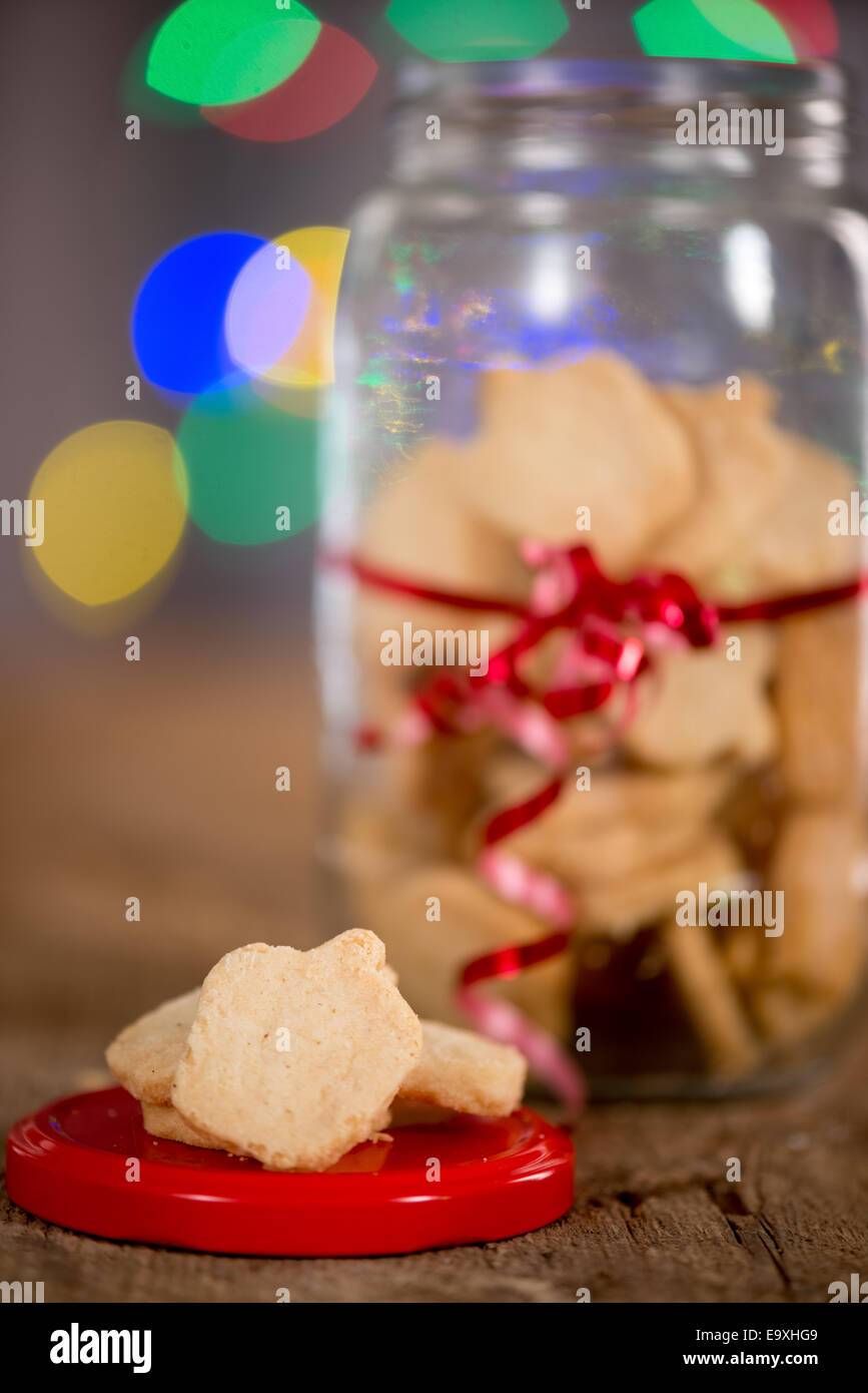 A jar of Hanukkah ( or holiday ) cookies with out of focus lights in background - Stock Image