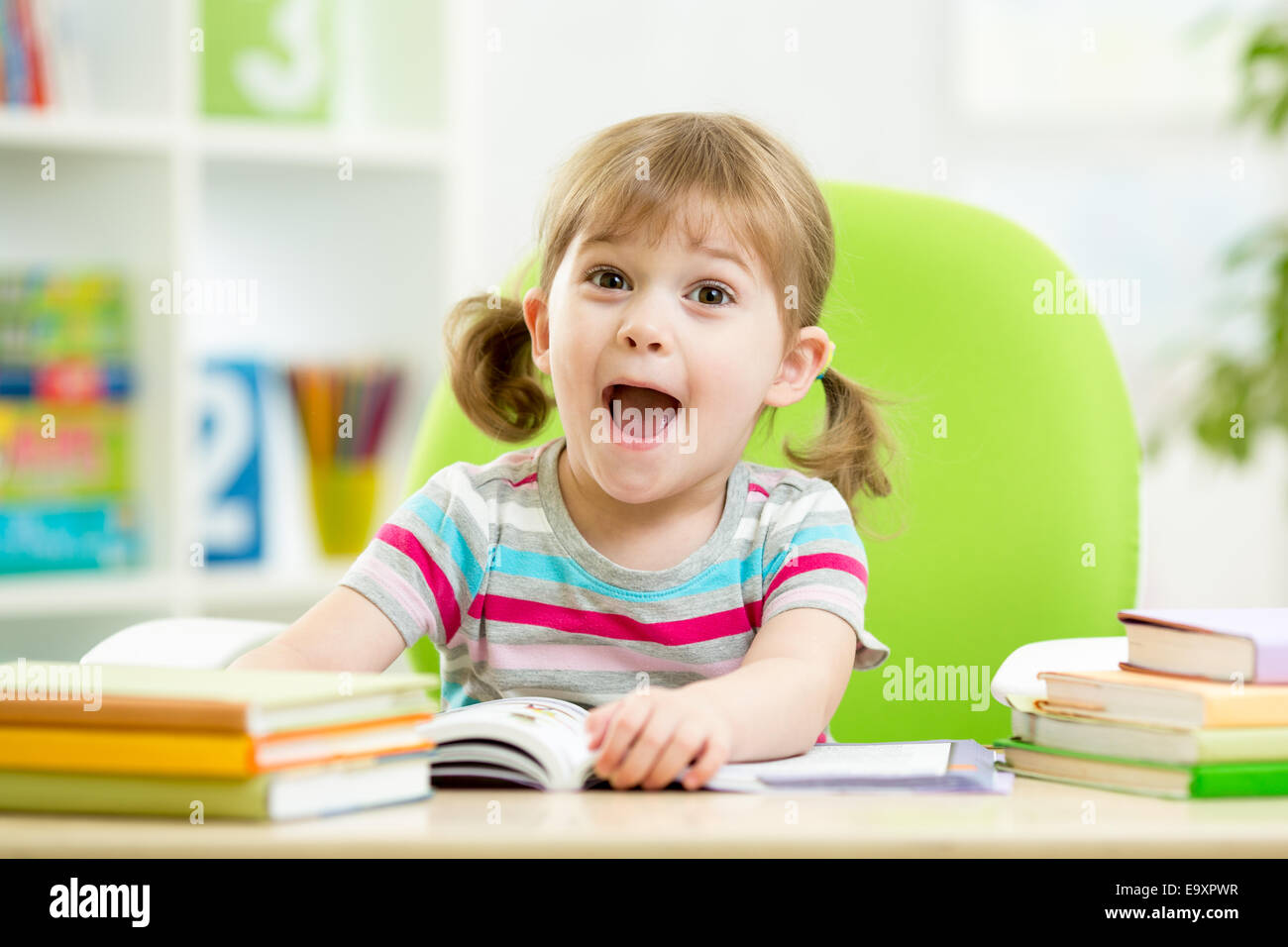 Happy kid reading book at table in nursery - Stock Image