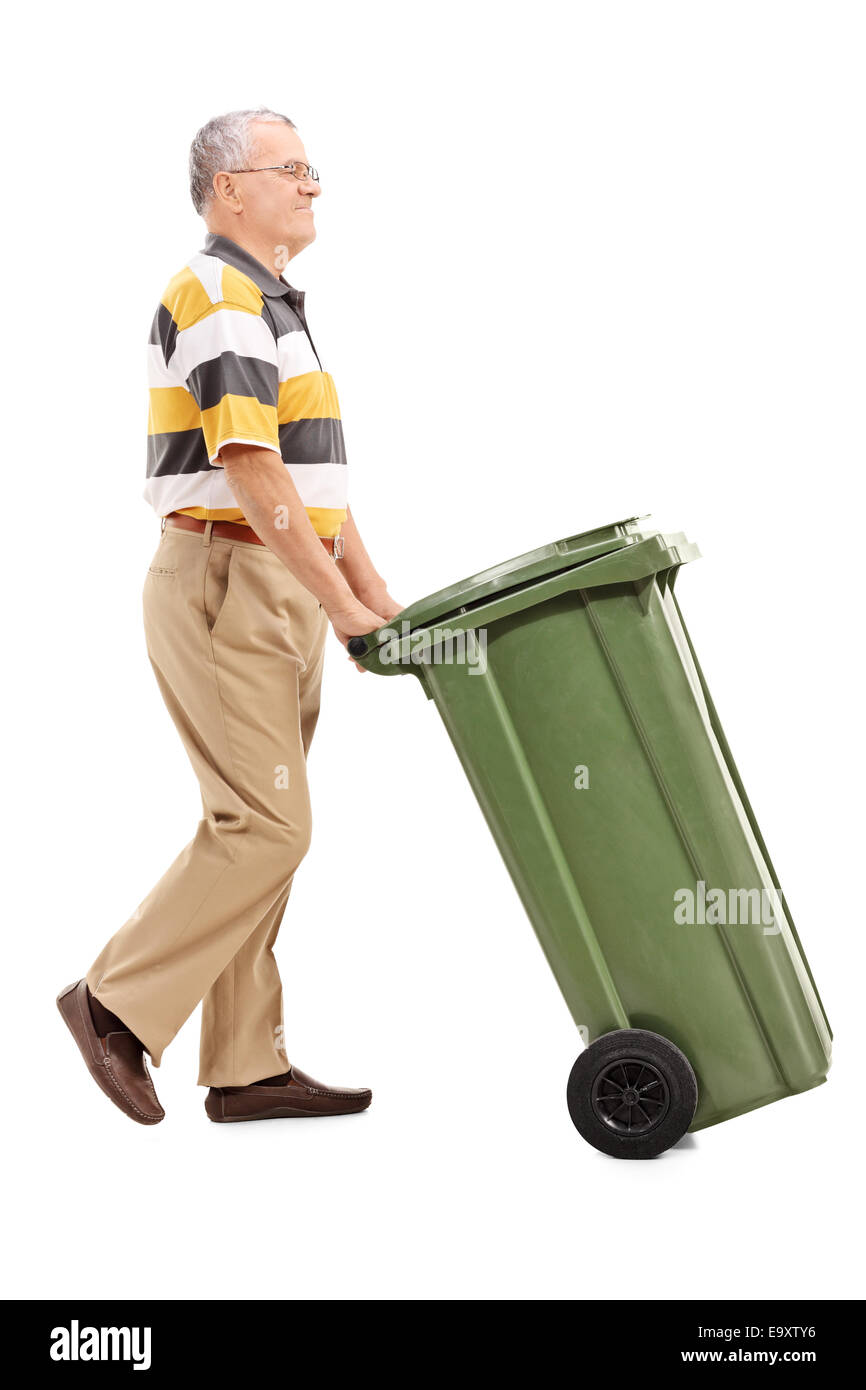 Full length portrait of a senior pushing a large green trash can isolated on white background - Stock Image