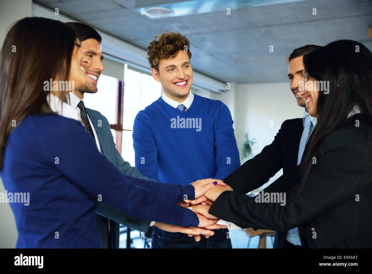 Smiling co-workers making pile of hands and looking at each other - Stock Image