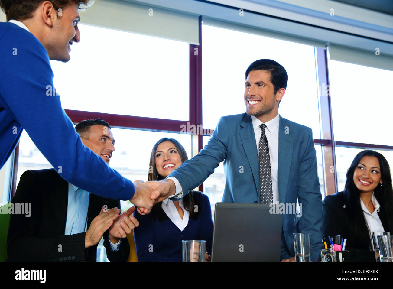 Business people sitting at the table while two of them shaking hands - Stock Image