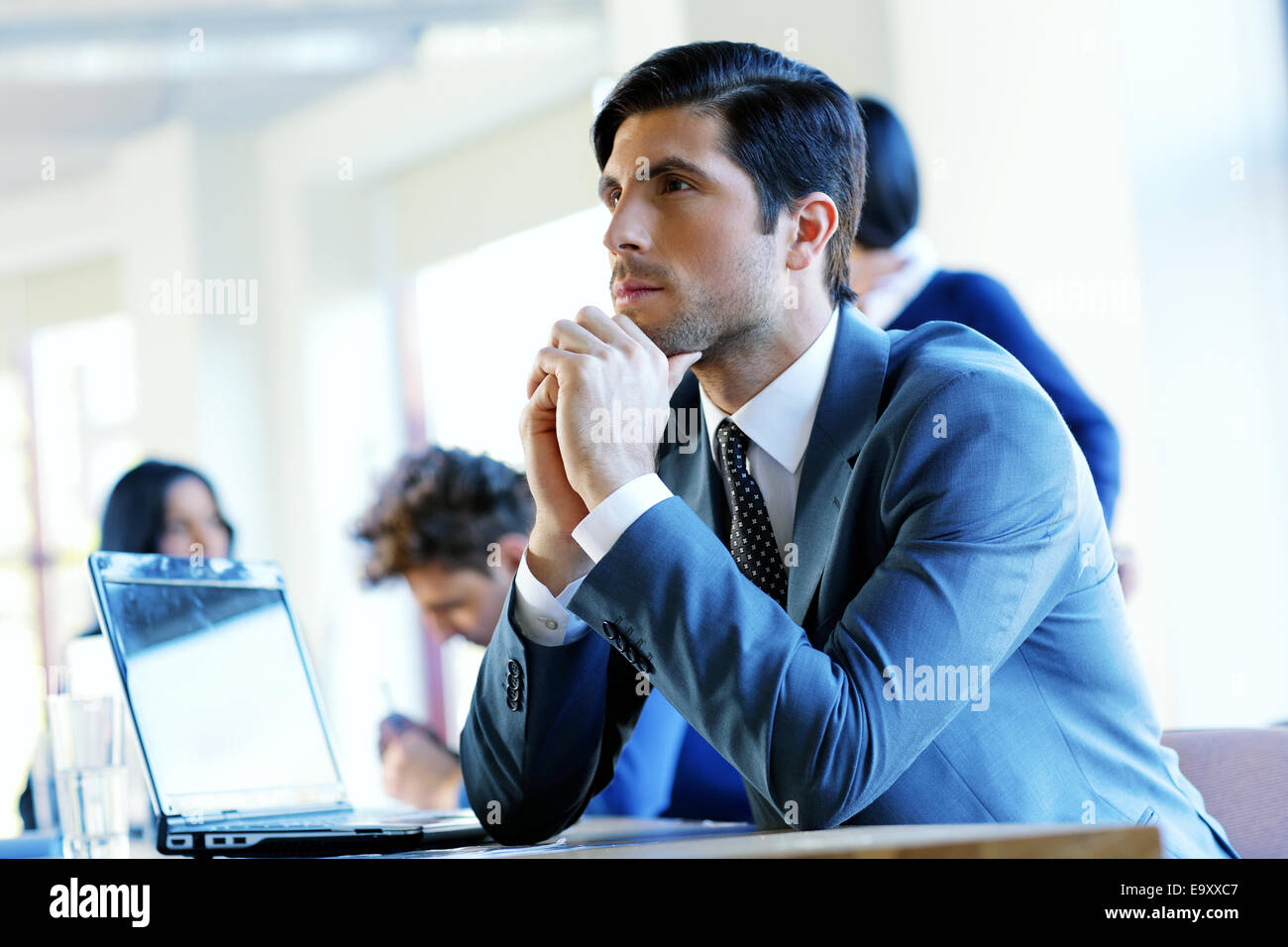 Portrait of a pensive businessman sitting at the table in office - Stock Image