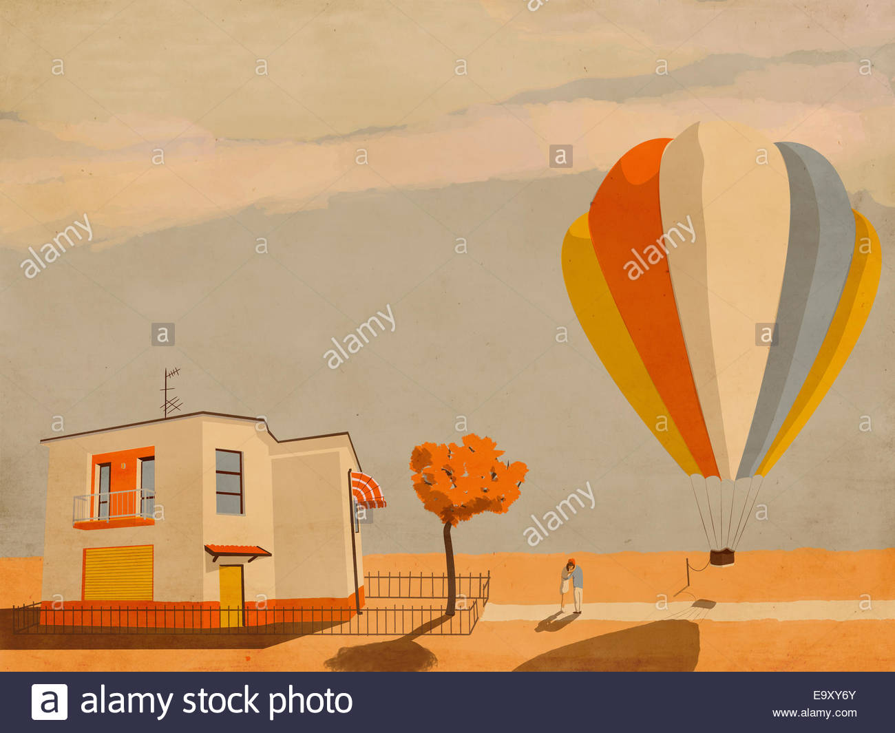 Couple hugging goodbye beside tethered hot air balloon - Stock Image