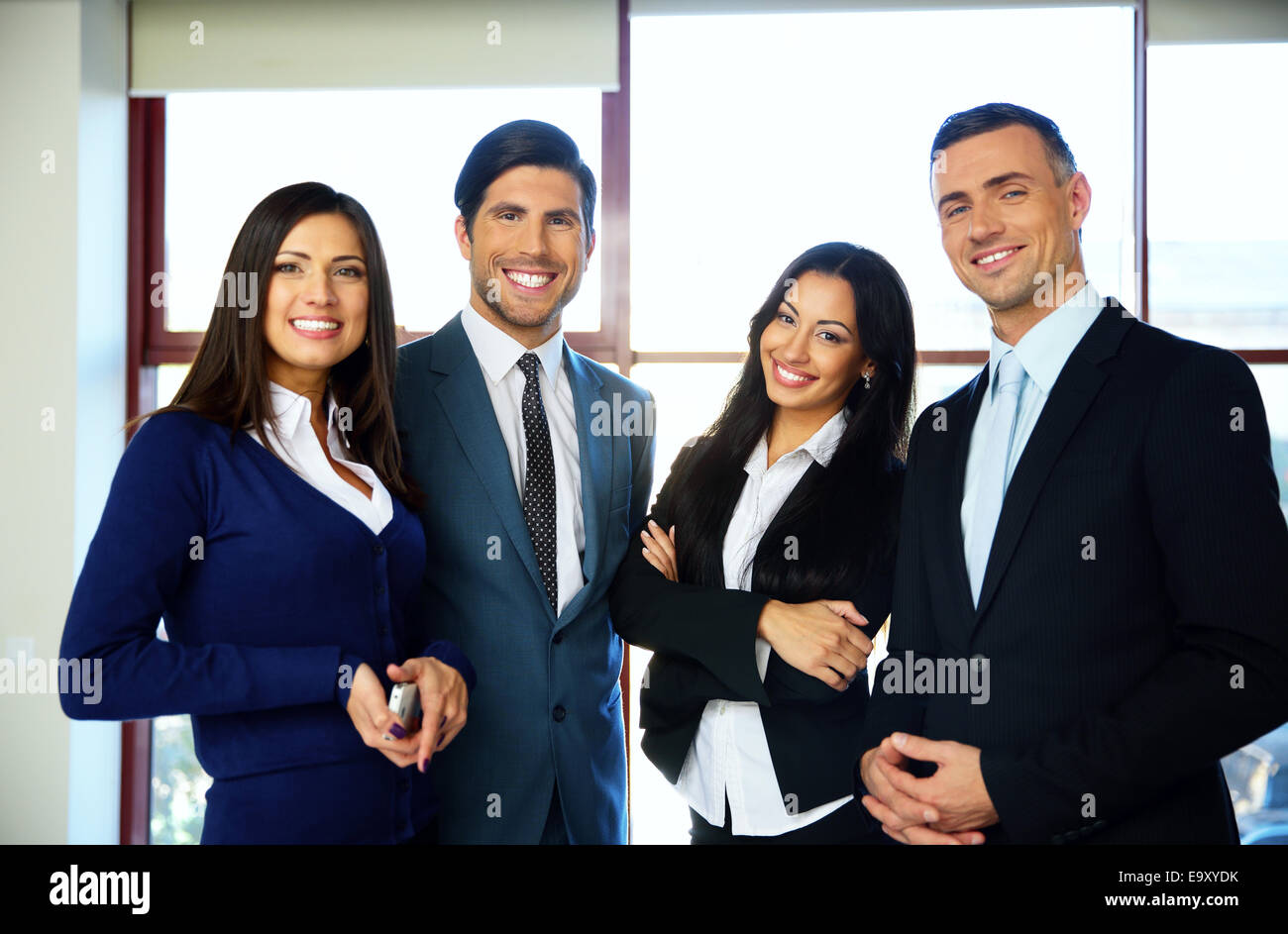 Group of cheerful business people standing in office - Stock Image