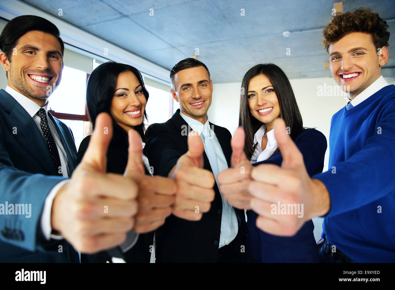 Portrait of happy young business people with thumbs up sign - Stock Image