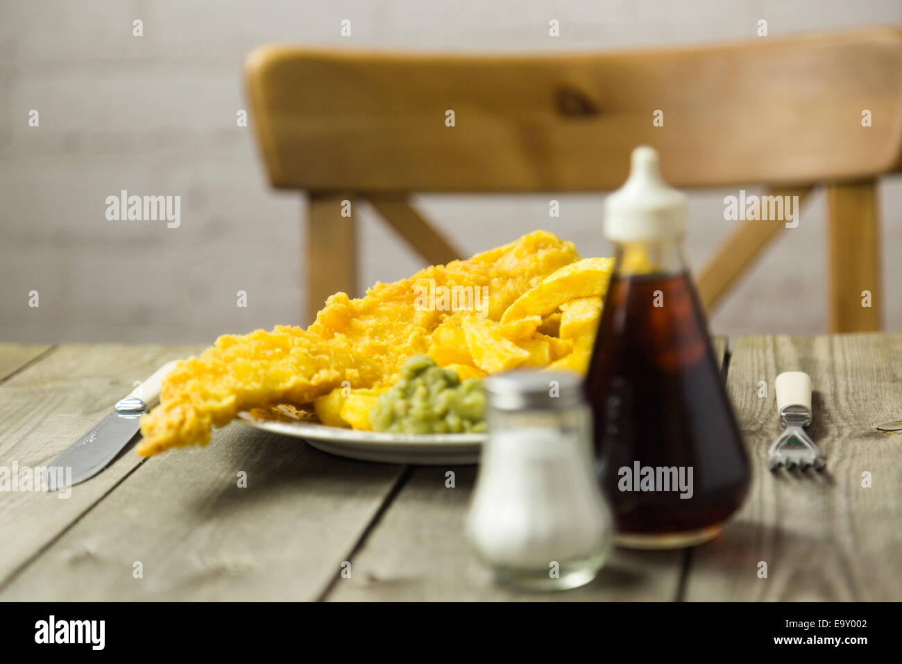 Traditional British takeaway meal of fish and chips with mushy peas on a newsprint plate - Stock Image