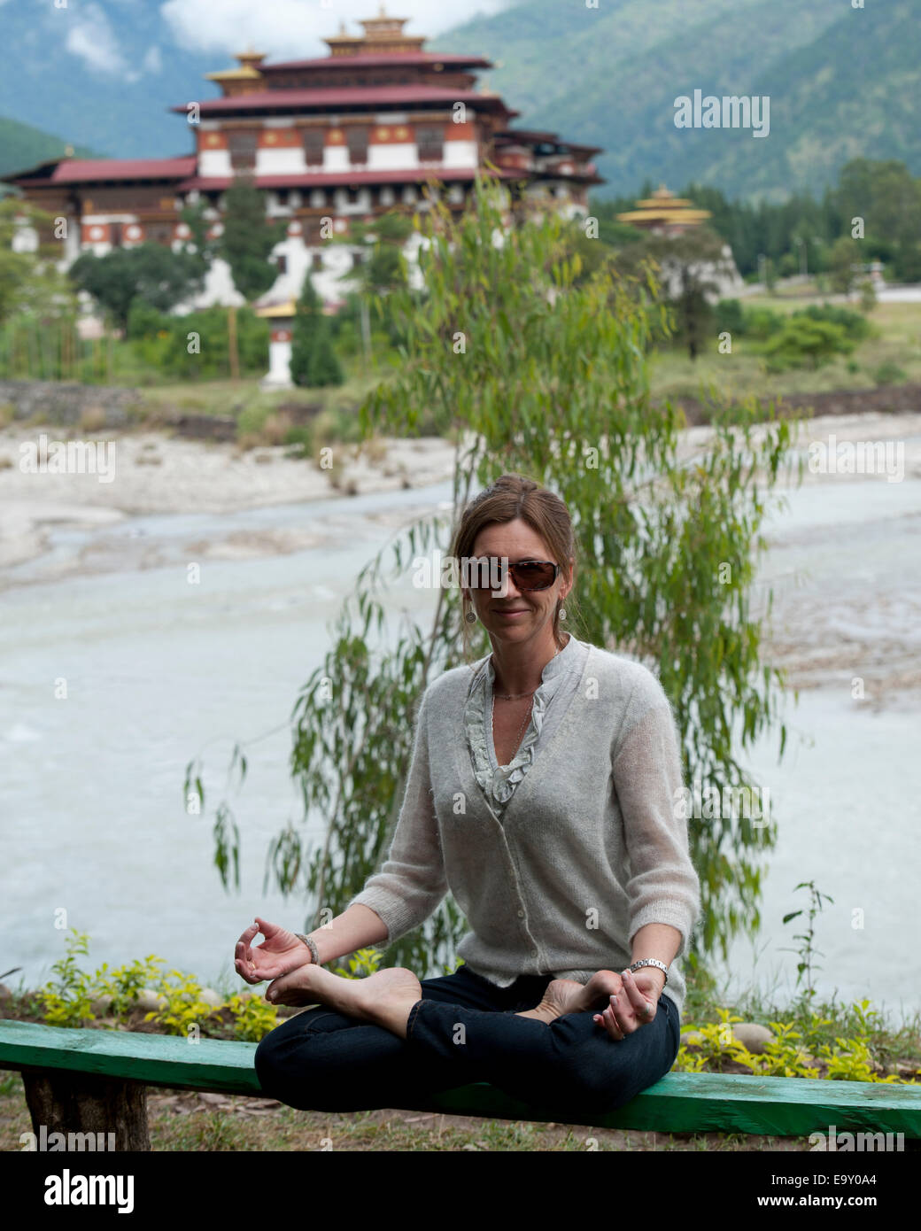 Woman meditating with Punakha Monastery in the background, Punakha, Bhutan - Stock Image