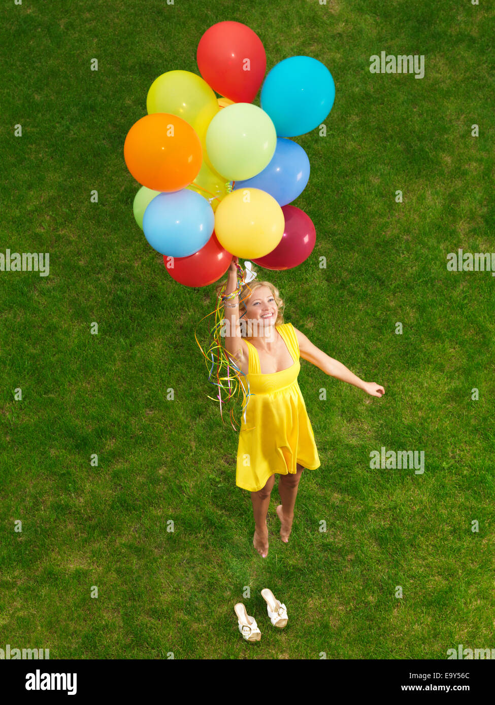 Young happy woman flying up from the ground on colorful air balloons - Stock Image