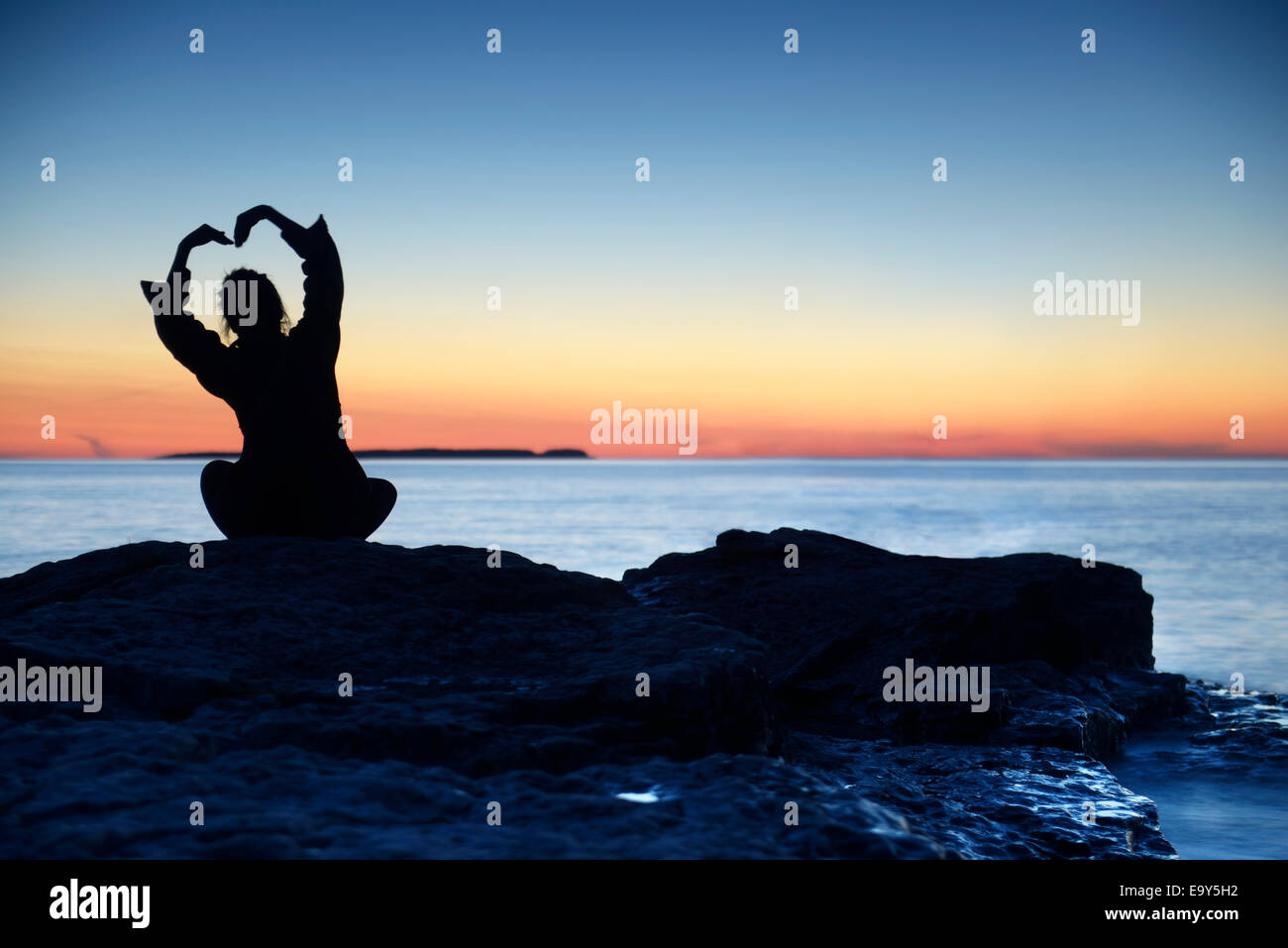 Silhouette of a woman sitting alone an a shore at sunset with her hands raise in a shape of a flower above her head, - Stock Image