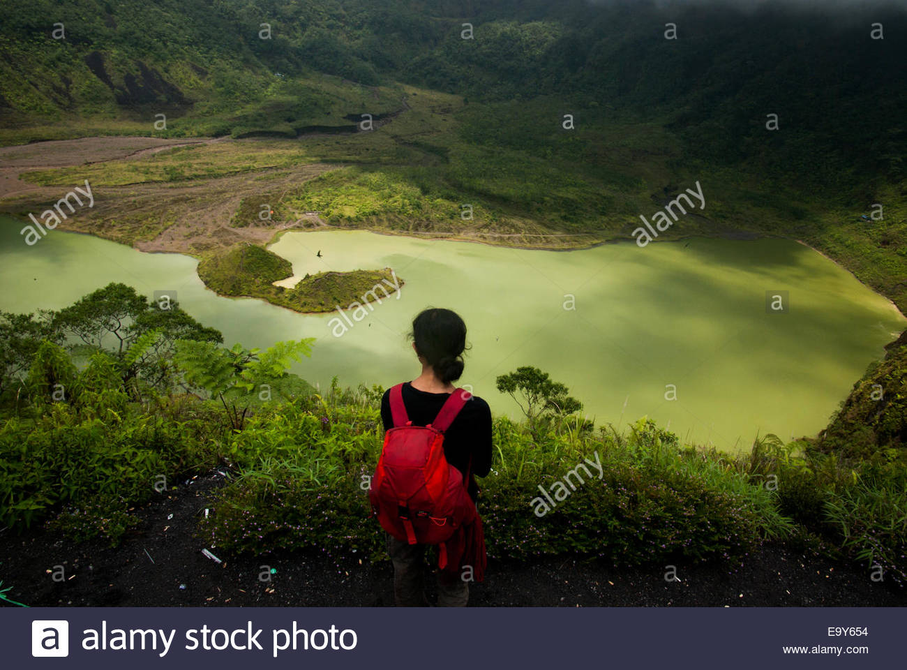 Female climber examines the caldera of Mount Galunggung volcano in West Java, Indonesia. © Reynold Sumayku - Stock Image