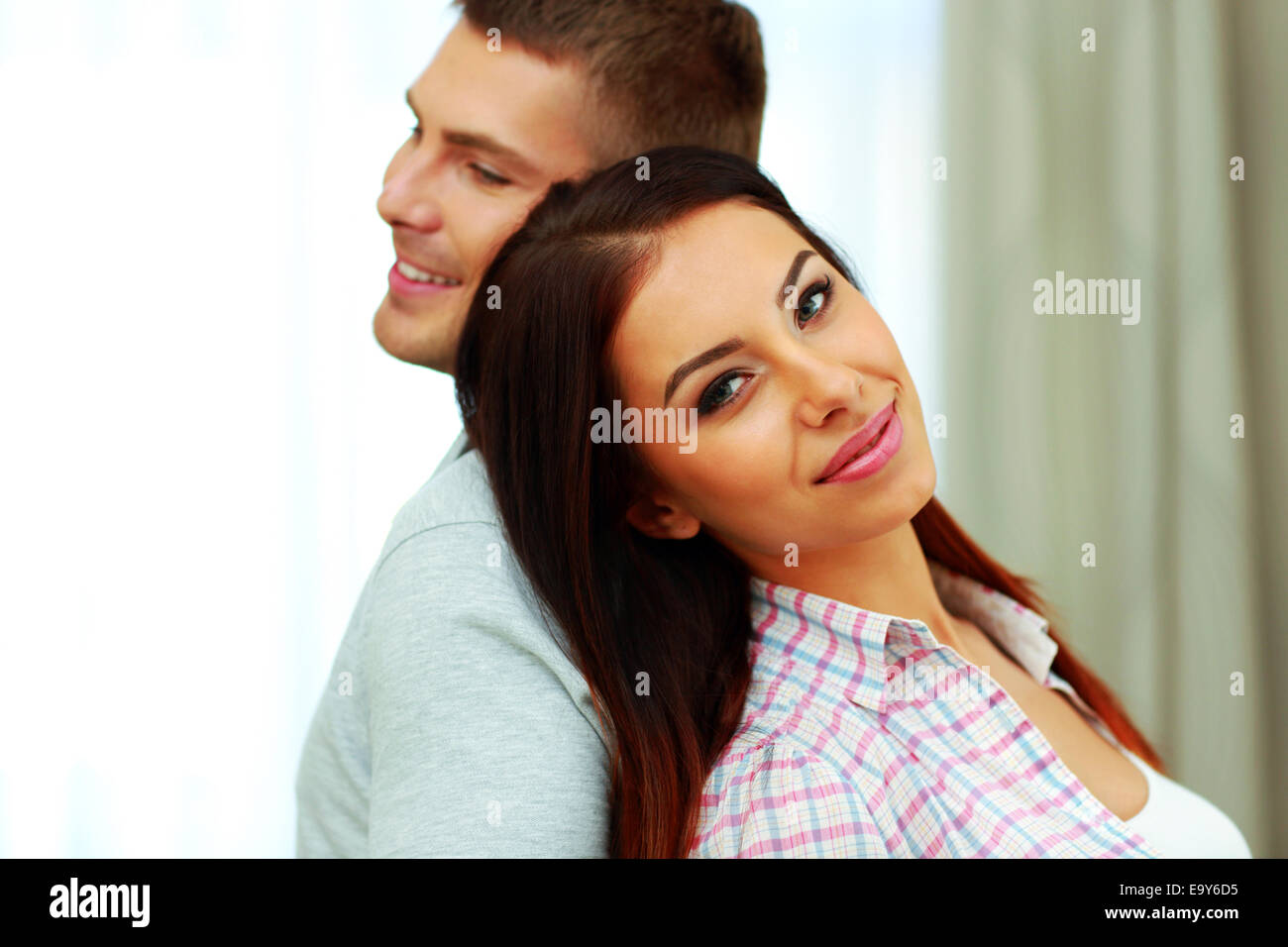 Young happy couple standing back to back - Stock Image