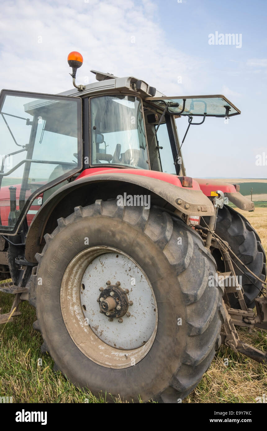 Close image of a red tractor on a field. - Stock Image
