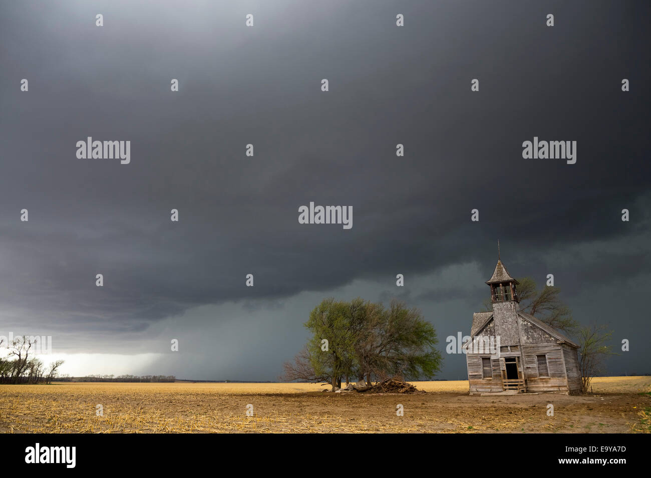 Outflow behind a tornado warned supercell approaches an old weathered school house in eastern Nebraska. - Stock Image