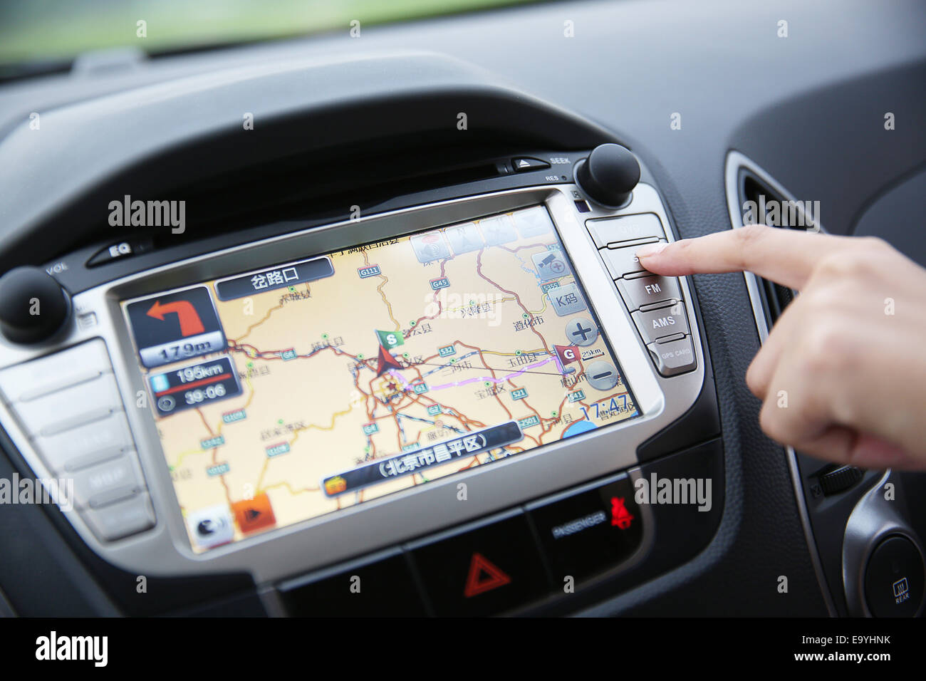 Human finger pointing to GPS map in a car - Stock Image